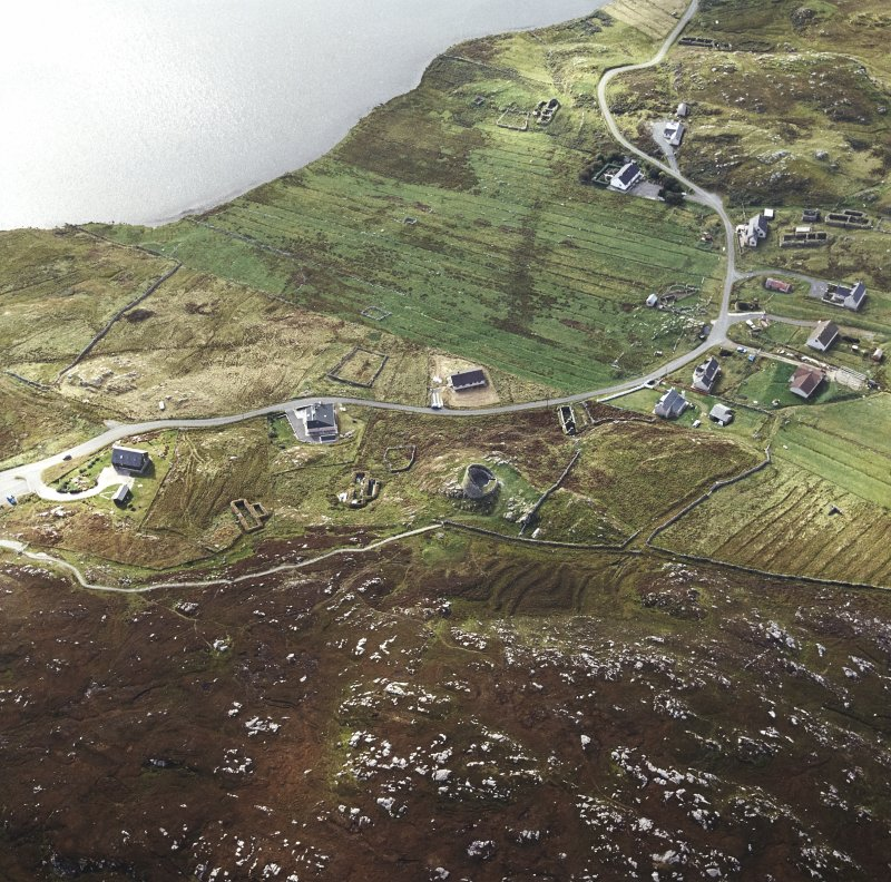 Oblique aerial view centred on the remains of the broch with the remains of the blackhouse and township adjacent, taken from the NE.