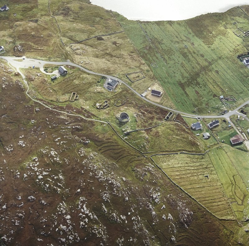 Oblique aerial view centred on the remains of the broch with the remains of the blackhouse and township adjacent, taken from the N.