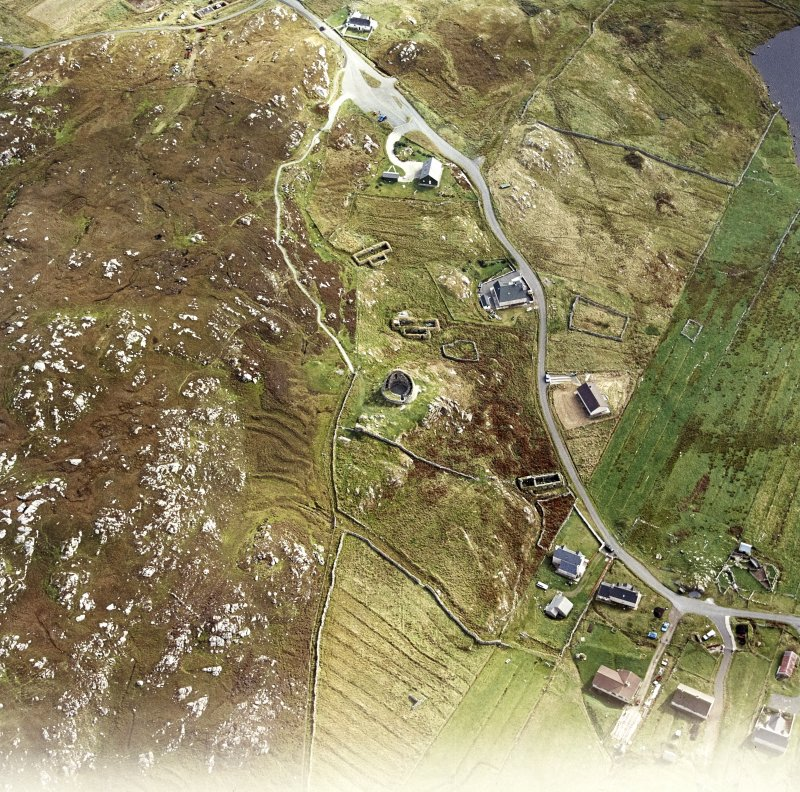 Oblique aerial view centred on the remains of the broch with the remains of the blackhouse and township adjacent, taken from the NW.