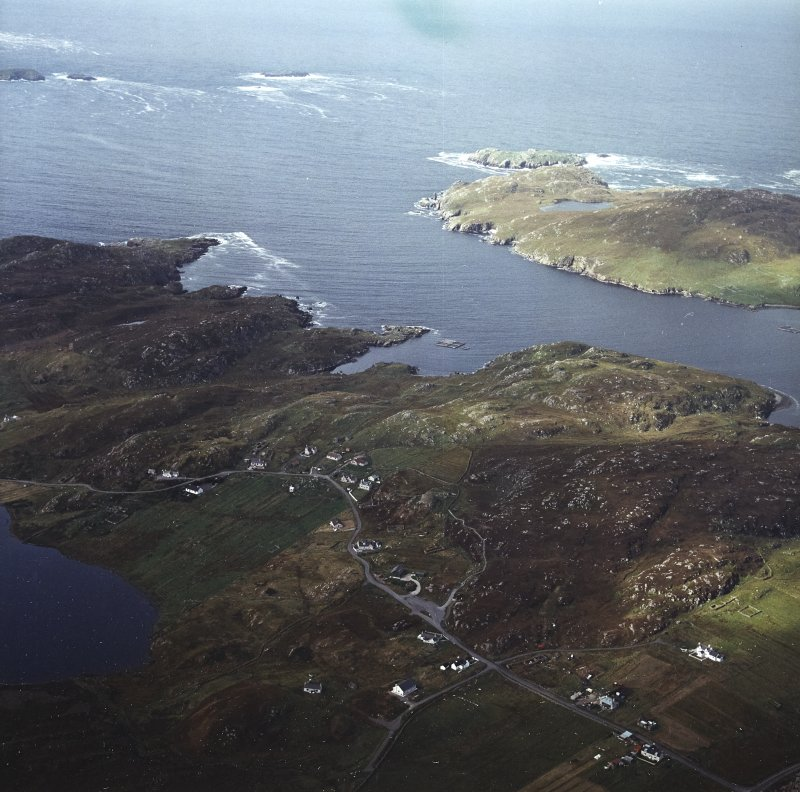 General oblique aerial view looking across the remains of the broch with the remains of the blackhouse and township adjacent, taken from the SE.