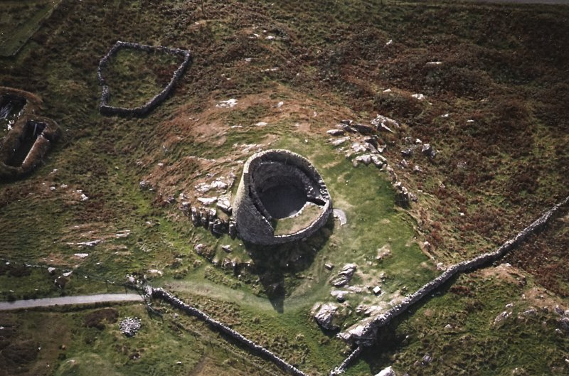 Oblique aerial view centred on the remains of the broch, taken from the NNE.