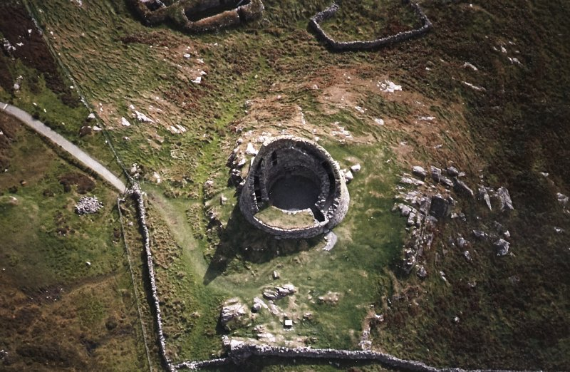 Oblique aerial view centred on the remains of the broch, taken from the NNW.