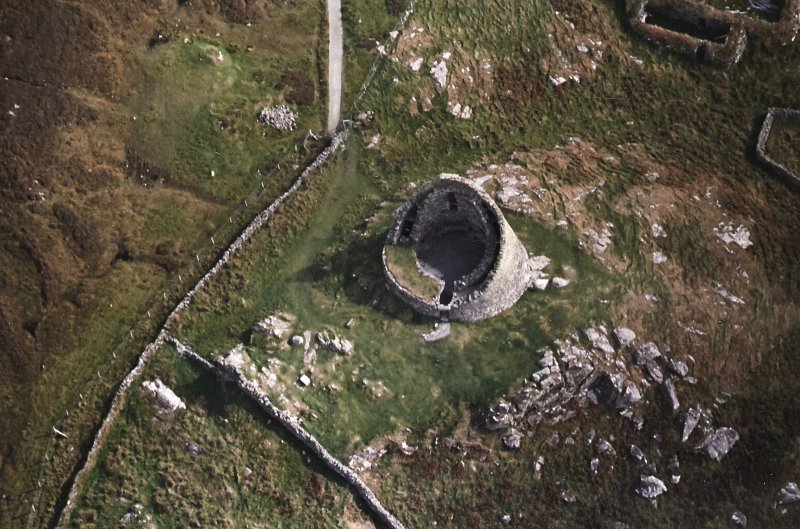 Oblique aerial view centred on the remains of the broch, taken from the WNW.