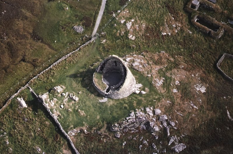 Oblique aerial view centred on the remains of the broch, taken from the W.