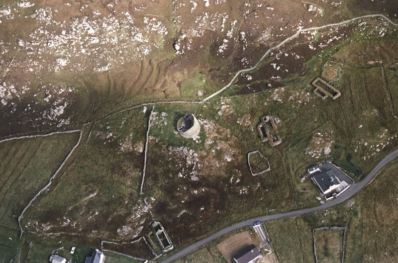 Oblique aerial view centred on the remains of the broch with the remains of the blackhouse and township adjacent, taken from the SW.