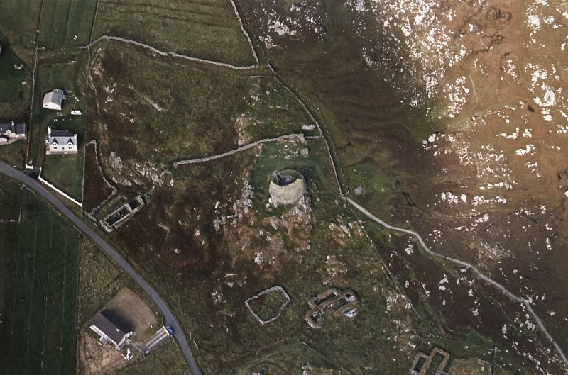 Oblique aerial view centred on the remains of the broch with the remains of the blackhouse and township adjacent, taken from the SSE.