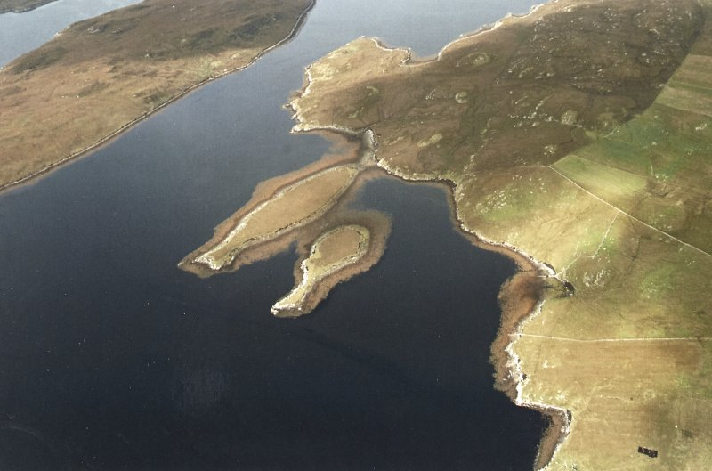 Oblique aerial view centred on the islands of Bratanish Mor and Bratanish Beag with the remains of lazy beds adjacent, taken from the SE.