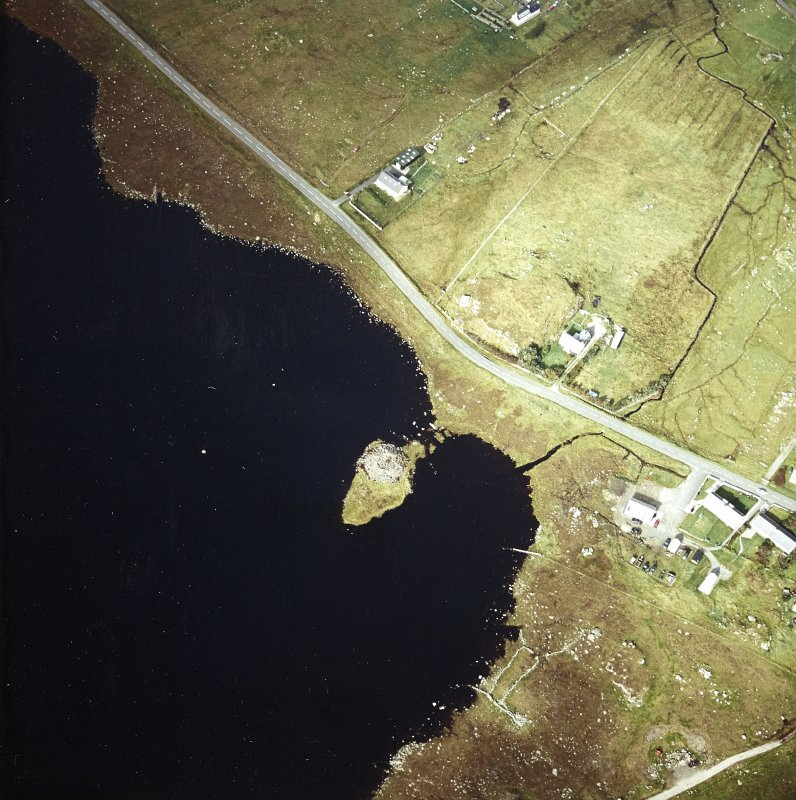 Oblique aerial view centred on remains of the broch with the possible crannog adjacent, taken from the SE.