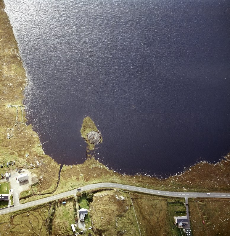 Oblique aerial view centred on remains of the broch with the possible crannog adjacent, taken from the N.