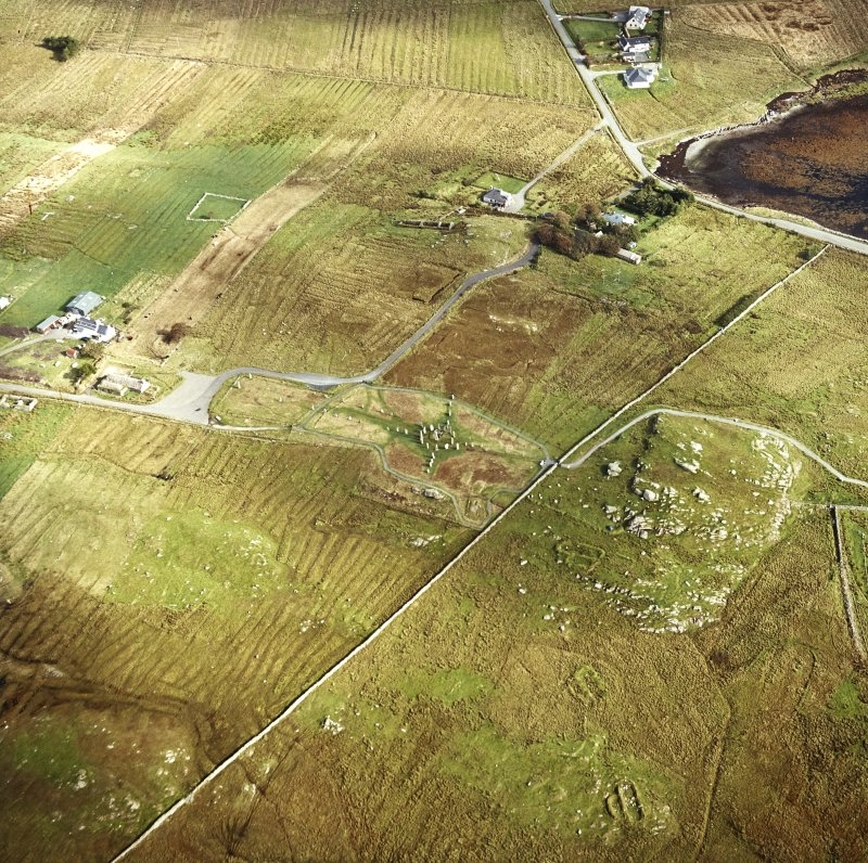 Oblique aerial view centred on the remains of the stone circle and stone alignments with the township and lazy beds adjacent, taken from the W.