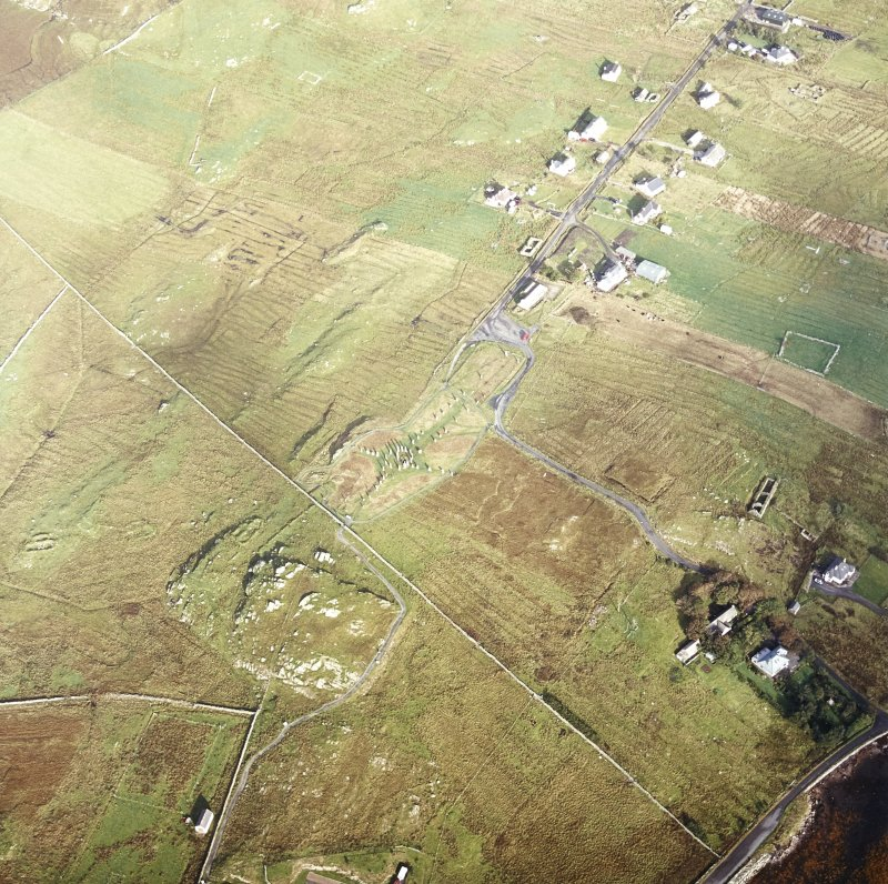 Oblique aerial view centred on the remains of the stone circle, chambered cairn and stone alignments with the township and lazy beds adjacent, taken from the SSE.