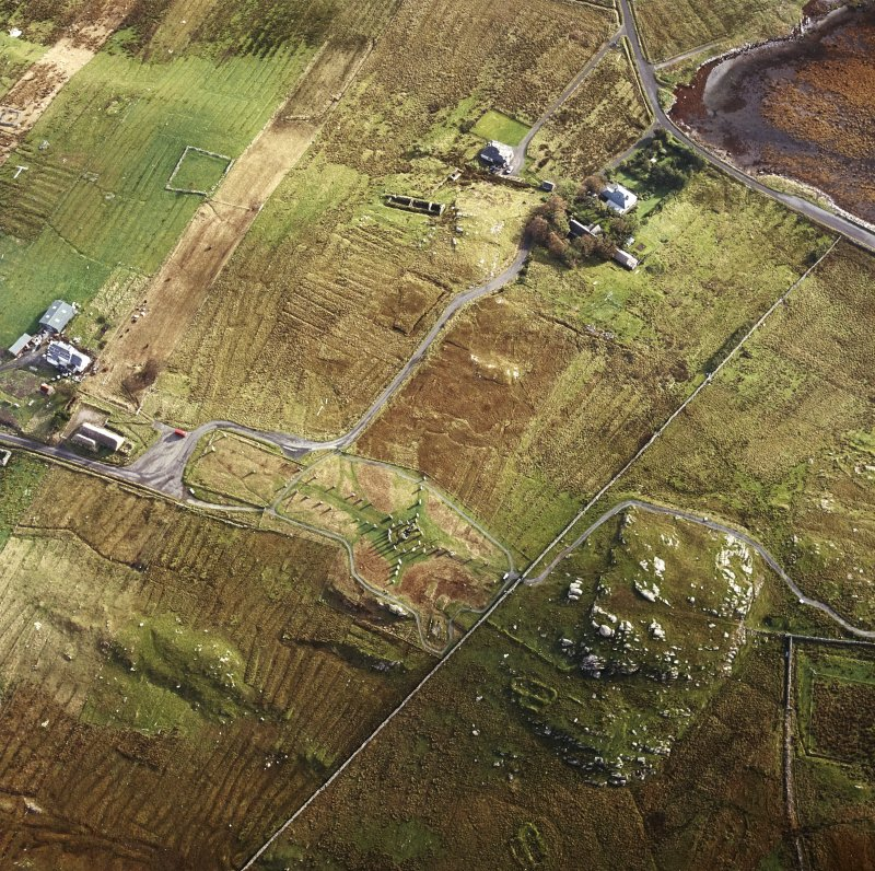 Oblique aerial view centred on the remains of the stone circle, chambered cairn and stone alignments with the township and lazy beds adjacent, taken from the WSW.