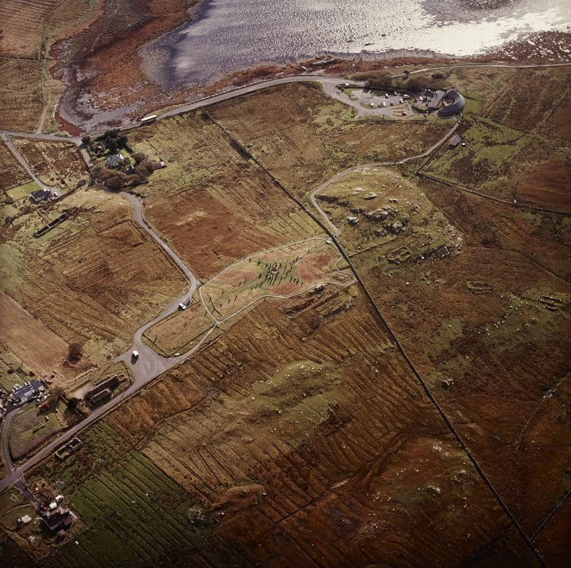 Oblique aerial view centred on the remains of the stone circle, chambered cairn and stone alignments with the township and lazy beds adjacent, taken from the NW.