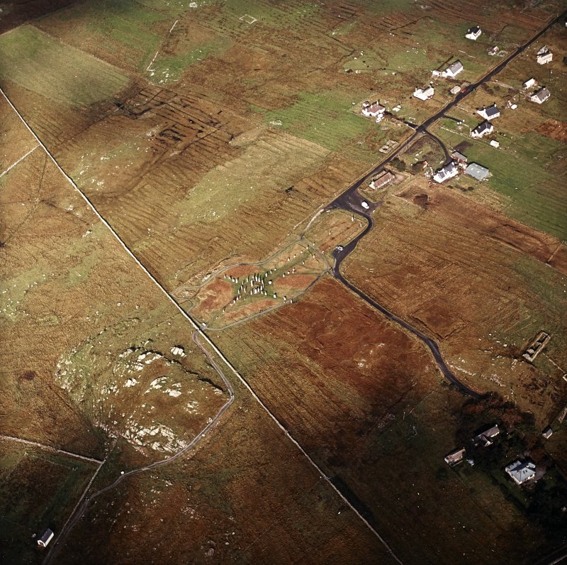 Oblique aerial view centred on the remains of the stone circle, chambered cairn and stone alignments with the township and lazy beds adjacent, taken from the SE.