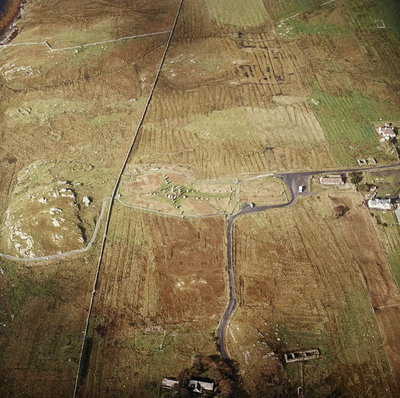Oblique aerial view centred on the remains of the stone circle, chambered cairn and stone alignments with the township and lazy beds adjacent, taken from the ESE.