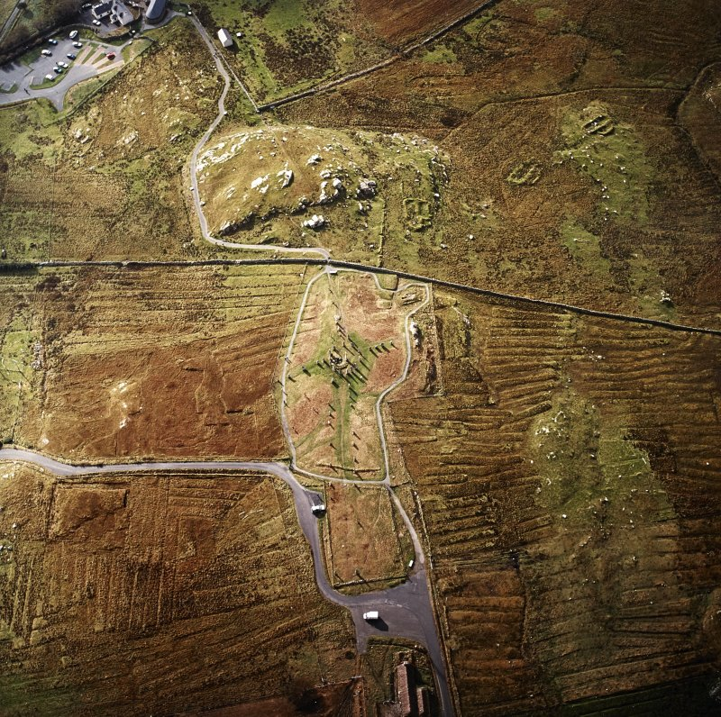 Oblique aerial view centred on the remains of the stone circle, chambered cairn and stone alignments with the township and lazy beds adjacent, taken from the NNE.