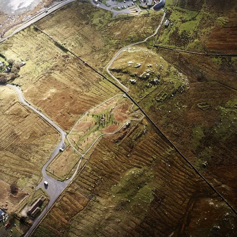 Oblique aerial view centred on the remains of the stone circle, chambered cairn and stone alignments with the township and lazy beds adjacent, taken from the NNW.
