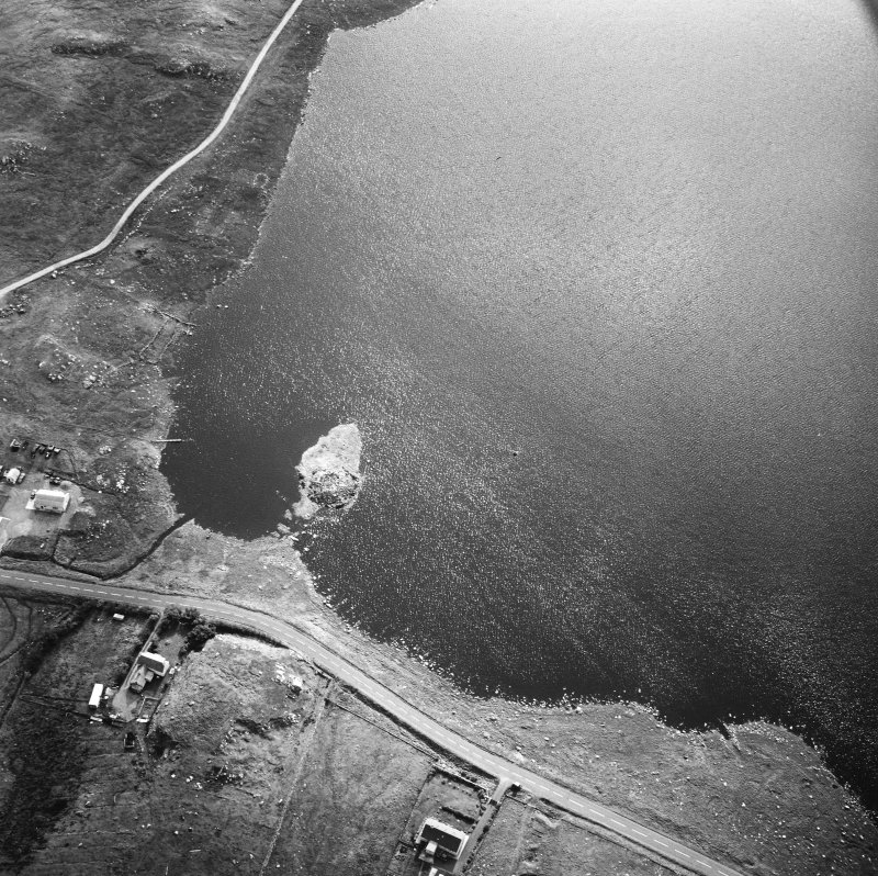 Oblique aerial view centred on remains of the broch with the possible crannog adjacent, taken from the NW.