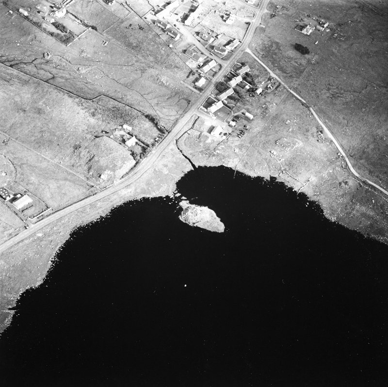 Oblique aerial view centred on remains of the broch with the possible crannog adjacent, taken from the SW.