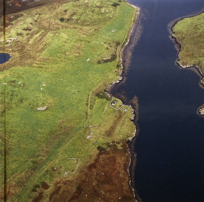 Oblique aerial view centred on the remains of the church and burial ground with the remains of the township adjacent, taken from the WSW.