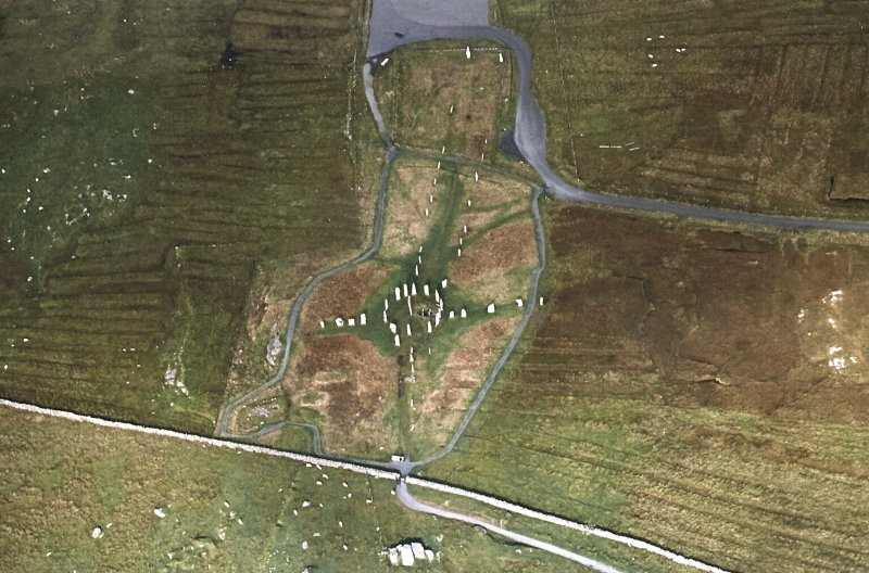 Oblique aerial view centred on the remains of the stone circle, stone alignments and chambered cairn, taken from the S.