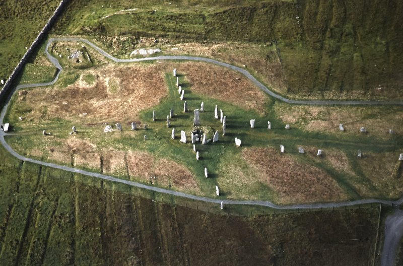 Oblique aerial view centred on the remains of the stone circle, stone alignments and chambered cairn, taken from the ESE.