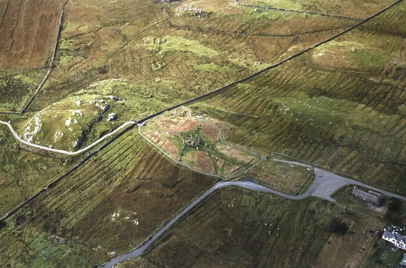 Oblique aerial view centred on the remains of the stone circle, stone alignments and chambered cairn with the remains of the township and lazy beds adjacent, taken from the NE.