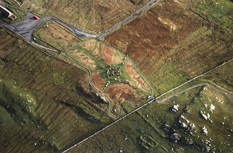 Oblique aerial view centred on the remains of the stone circle, chambered cairn and stone alignments with lazy beds adjacent, taken from the WSW.
