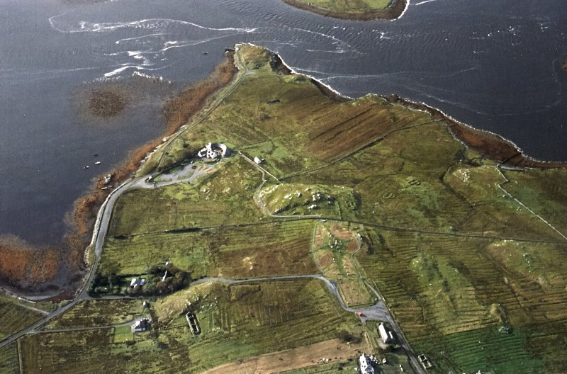 General oblique aerial view centred on the remains of the stone circle, chambered cairn and stone alignments with the farmhouse, visitor centre and township adjacent, taken from the NNE.