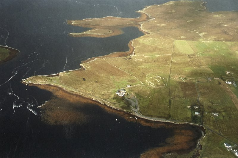 General oblique aerial view centred on the remains of the stone circle, chambered cairn and stone alignments with the farmhouse, visitor centre and township adjacent, taken from the ESE.
