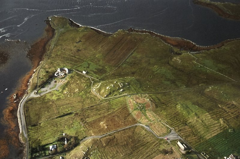 General oblique aerial view centred on the remains of the stone circle, chambered cairn and stone alignments with the farmhouse, visitor centre and township adjacent, taken from the NE.