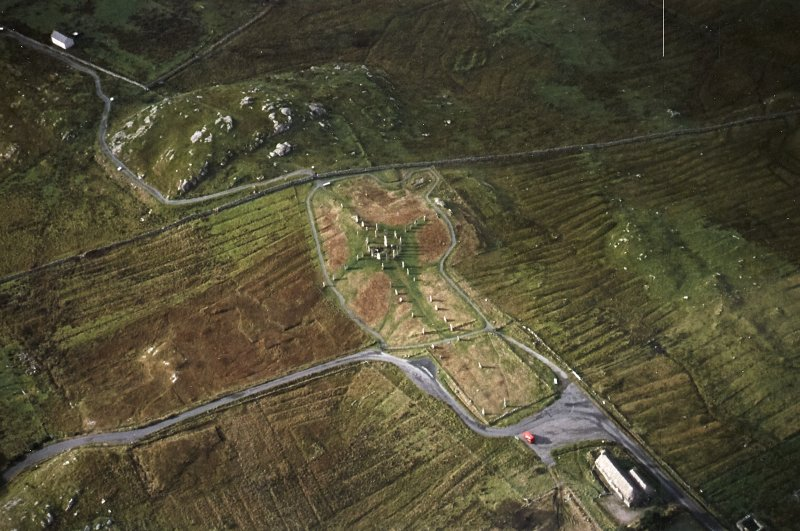 Oblique aerial view centred on the remains of the stone circle, chambered cairn and stone alignments with the blackhouse and lazy beds adjacent, taken from the NE.