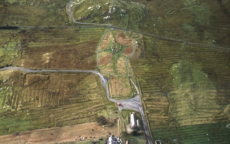 Oblique aerial view centred on the remains of the stone circle, chambered cairn and stone alignments with the blackhouse and lazy beds adjacent, taken from the NNE.