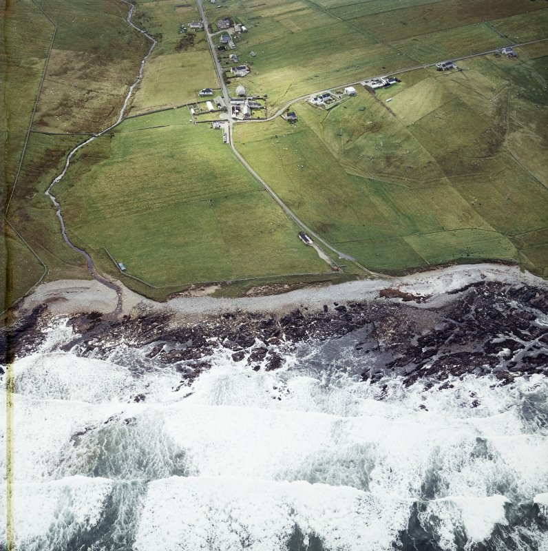 Oblique aerial view centred on the site of the settlement and cemetery with the crofting township and lazy beds adjacent, taken from the N.