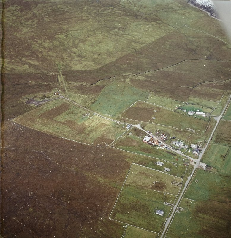 Oblique aerial view centred on the standing stone with the remains of the crofting township adjacent, taken from the ESE.