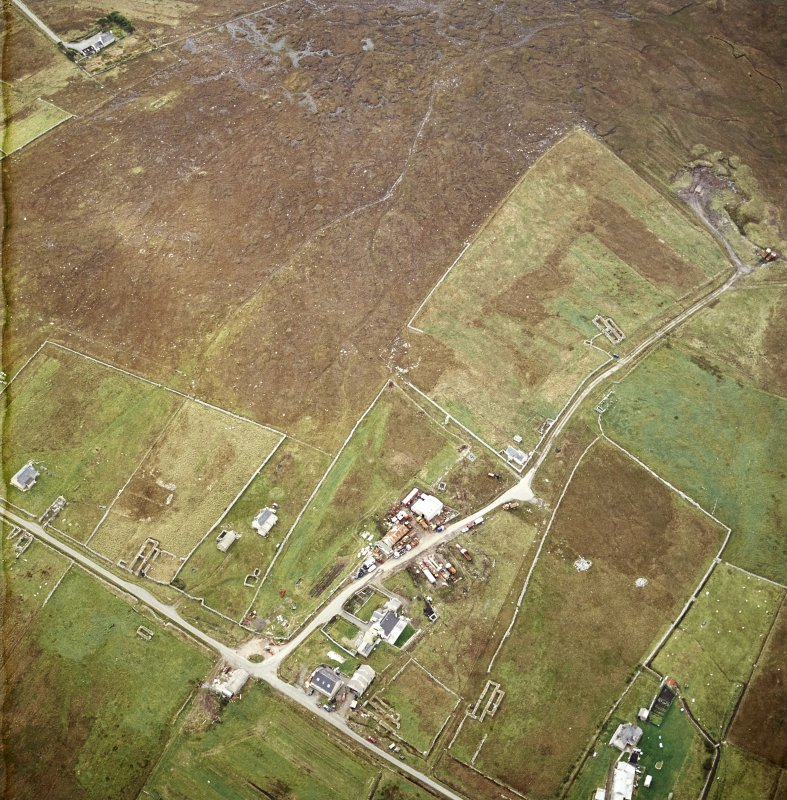 Oblique aerial view centred on the standing stone with the remains of the crofting township adjacent, taken from the NNE.