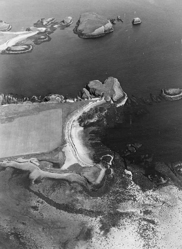 Oblique aerial view centred on the remains of the fort, settlement and lazy beds, with remains of rig cultivation adjacent, taken from the NW.