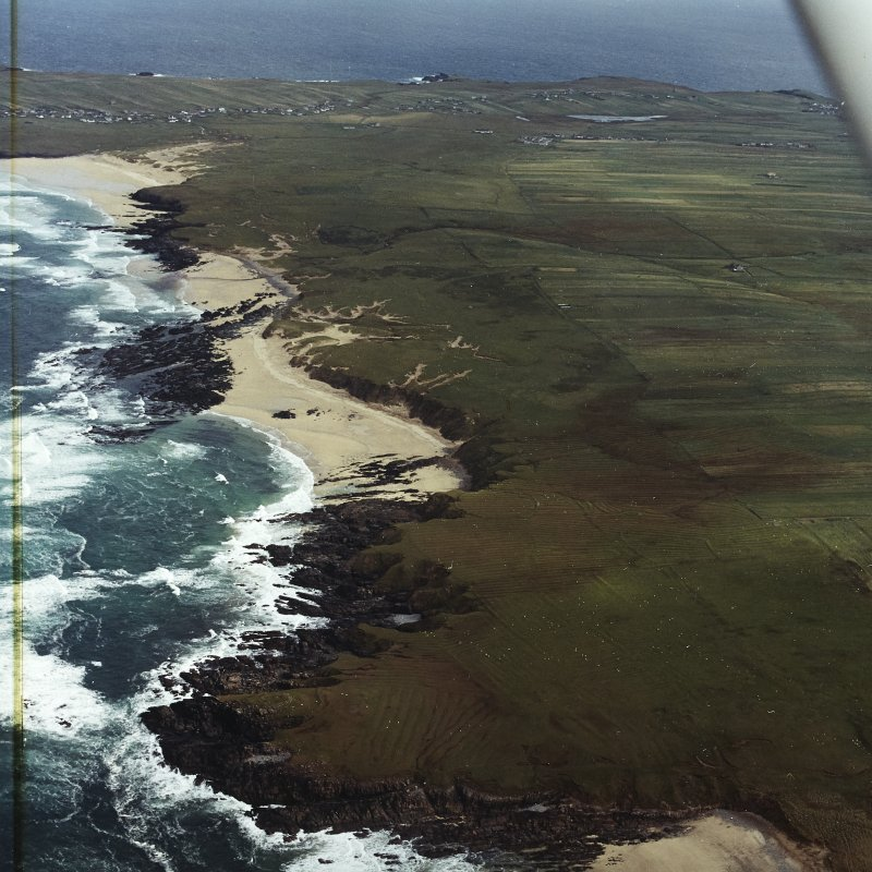 General oblique aerial view looking across the remains of the dun, building and the lazy beds along the west coast of Lewis towards Eoropie, taken from the WSW.