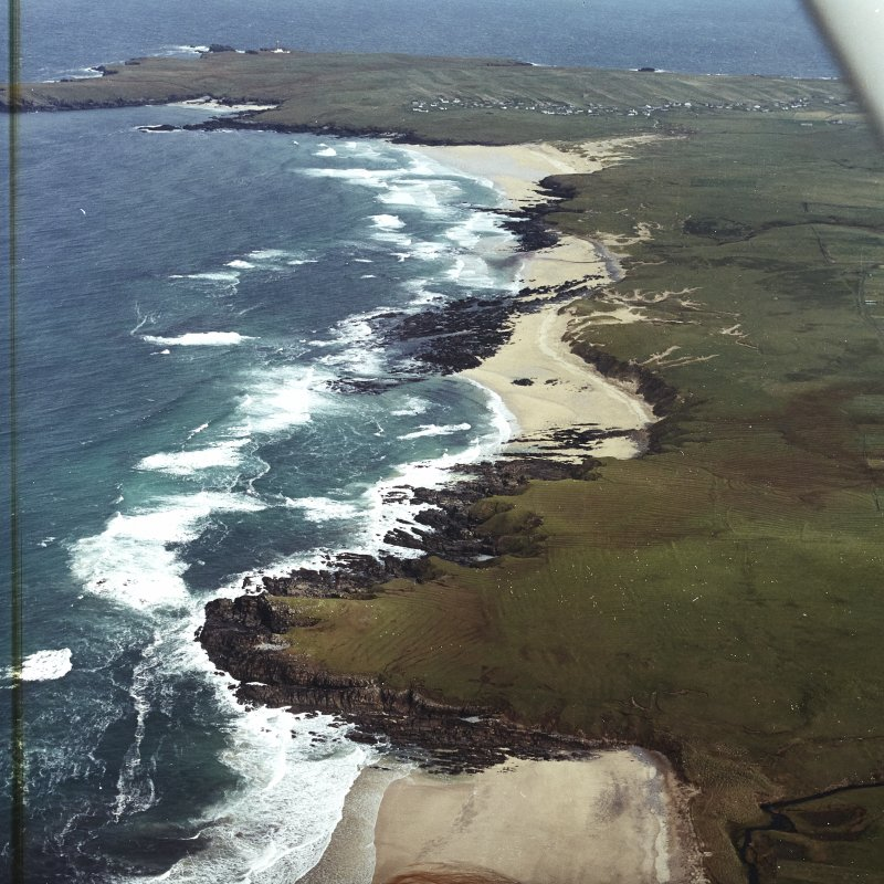 General oblique aerial view looking across the remains of the dun, building and the lazy beds along the west coast of Lewis towards Eoropie, taken from the SW.