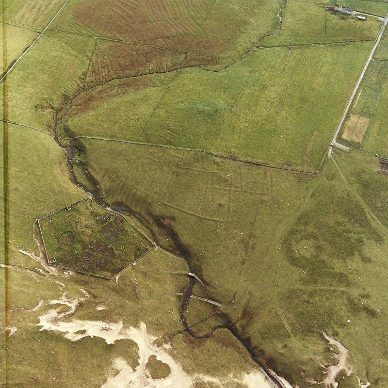 Oblique aerial view centred on the remains of the field system with the remains of the church, burial ground and corn mill adjacent, taken from the NW.