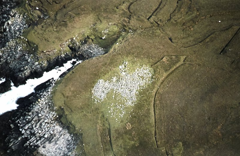 Oblique aerial view centred on the remains of the chambered cairn, taken from the WNW.