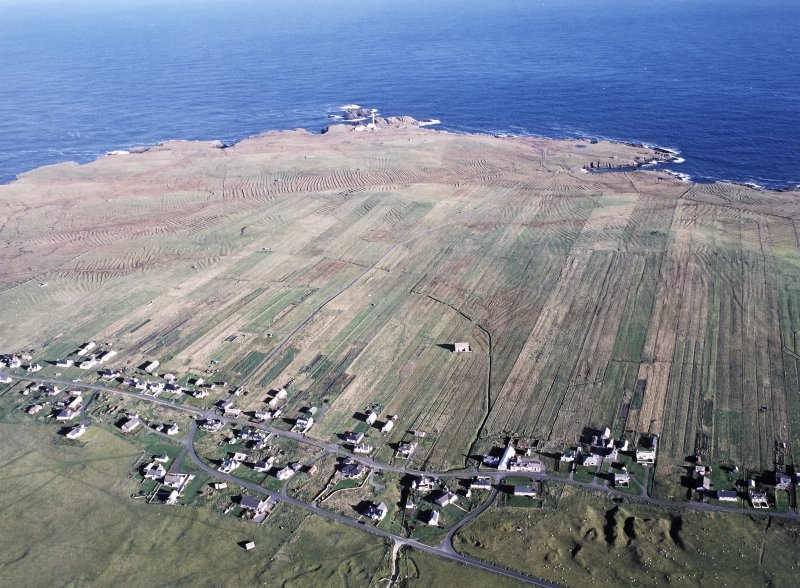 Oblique aerial view centred on St Moluag's chapel and township with lazy beds at Eoropie, Lewis and Butt of Lewis lighthouse adjacent, taken from the S.