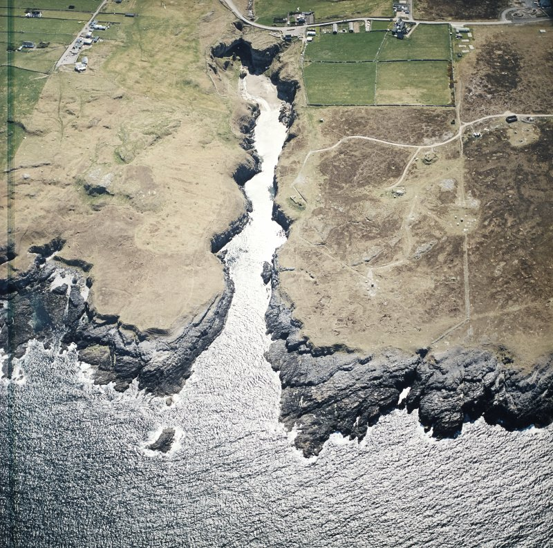 Oblique aerial view centred on the Smoo cave with the remains of the radar station and crofting townships adjacent, taken from the NNE.