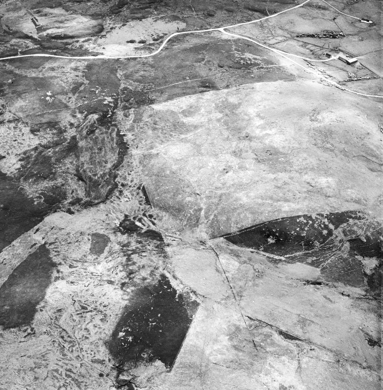 Breackue, Cnoc Dubh, oblique aerial view, taken from the NW, showing an area with small cairns and a trackway, a hut-circle and small cairns, as well as an enclosure, a hut and burnt mound in the centre of the photograph. An area with small cairns and a farmstead is visible in the upper left-hand corner.
