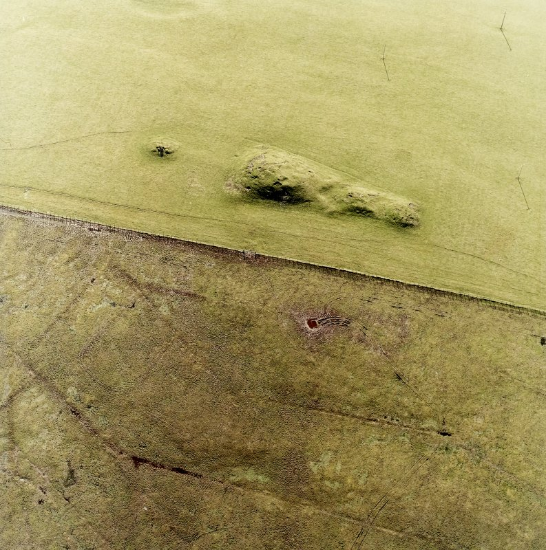 Oblique aerial view centred on the remains of the cairns, taken from the NE.