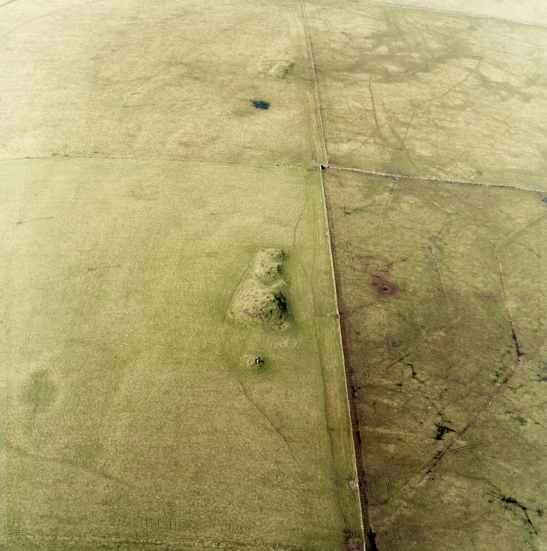Oblique aerial view centred on the remains of the cairns, taken from the SE.