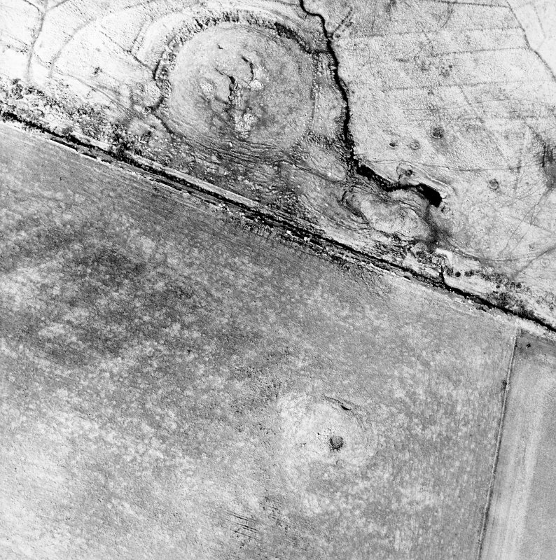 Oblique aerial view of the remains of the broch, cairn and sheepfolds, taken from the SE.