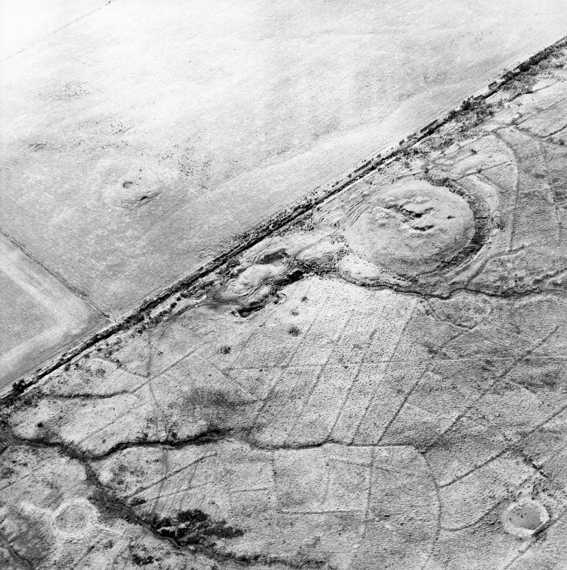 Oblique aerial view of the remains of the broch, cairn and sheepfolds, taken from the NNW.