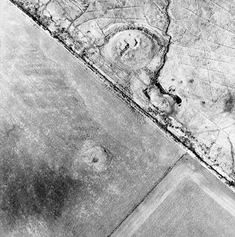 Oblique aerial view of the remains of the broch, cairn and sheepfolds, taken from the ESE.