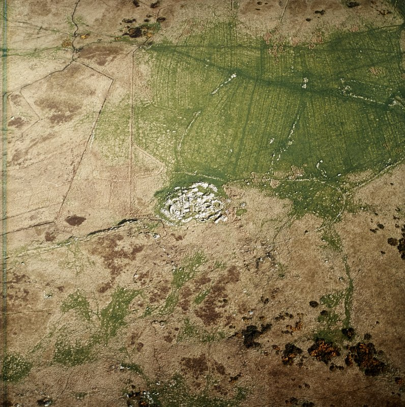 Oblique aerial view centred on the remains of the dun, settlement and field system with hut-circle and farmstead adjacent, taken from the W.
